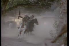 Bandits on horseback leaving burning village Stock Footage