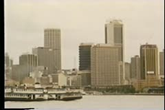 Wide shot ferry moving along river in front of cityscape - stock footage