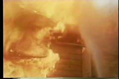 Firemen hosing down burning house Stock Footage