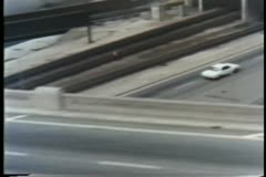 Aerial view of police cruiser chasing white car Stock Footage