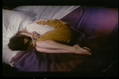 Upset woman curled up on bed - stock footage