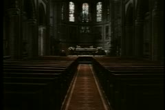Long shot looking down empty church aisle Stock Footage