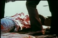 Loading bloody dead man into trunk of car Stock Footage