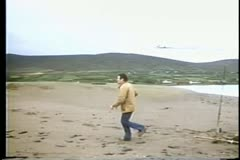 Rear view man standing on beach watching smoking airplane crash Stock Footage