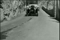 Vintage car driving off mountain and crashing into ocean Stock Footage