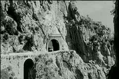 Long shot car driving out of mountain tunnel - stock footage