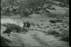 Wide shot cowboys on horseback on a wild chase Stock Footage