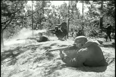 Side view soldiers in forest firing machine guns Stock Footage