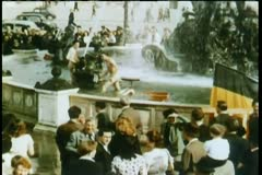 Men bathing in public fountain with crowd watching Stock Footage