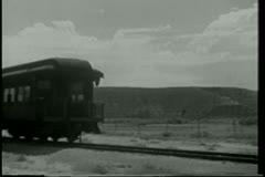 Wide shot cowboy on  horseback chasing train Stock Footage