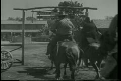 Rear view of cowboys on horseback riding into ranch - stock footage