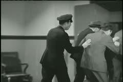 Policeman loading prisoners into paddy wagon Stock Footage