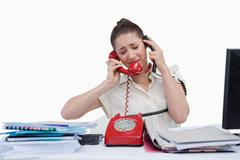 Stock Photo of Overburden businesswoman answering the phones