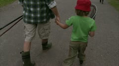 MS Father walking with son carrying landing net Stock Footage
