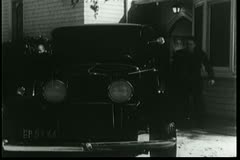 Men gettting into car and driving off Stock Footage
