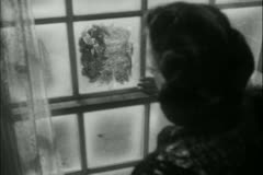 Woman looking out frosty window - stock footage