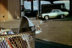 Bum taking shoe out of trash can - stock footage