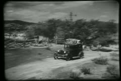 Vintage car piled with luggage arrives at country home Stock Footage