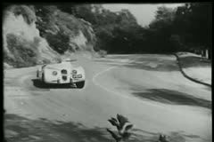 Two sports car racing down country road - stock footage