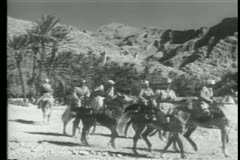 Moroccan cavalry charging through the desert Stock Footage