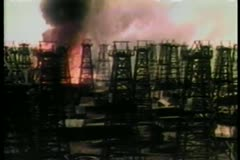 Oil refinery fire speading towards oil storage tanks Stock Footage