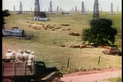 Cars and trucks driving through oil field Stock Footage