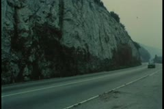 Car driving down mountain road through tunnel - stock footage