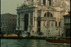 Gondola and vaporetto traveling down canal in Venice, Italy Stock Footage