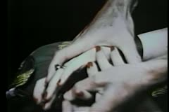 Close-up hands removing African pendant from dead woman's grasp Stock Footage