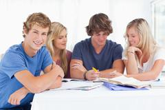 A group of students sitting together as they all study as one sits ahead a bit - stock photo