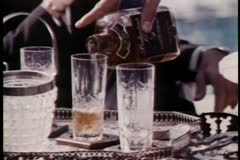 Close-up hand pouring liquor into glass and serving Stock Footage