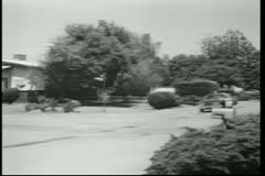 Police car racing down suburban street Stock Footage