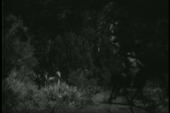 Native Americans on horseback riding through forest Stock Footage