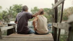 Old man and boy fishing together for fun on river - stock footage
