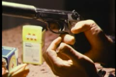 Hands loading gun with silencer Stock Footage