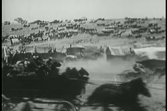 Covered wagon caravan rushing through prairie - stock footage