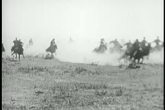 Men on horseback galloping through prairie - stock footage