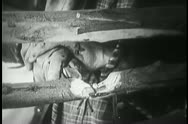 Close-up of bloody hands cutting through wood fence with knife Stock Footage