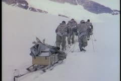 Rear view of men with sled trudging in snow Stock Footage