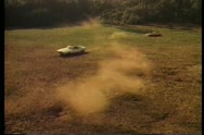 Two cars circling in open field Stock Footage