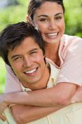 Close-up of a woman looking ahead while her friend is carrying her on his back Stock Photos
