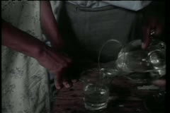 Close-up of hand pouring water from pitcher in glass Stock Footage