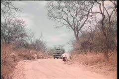 Truck narrowly missing woman walking on dirt road Stock Footage