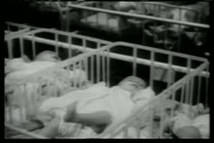Rows of babies in cribs in hospital - stock footage
