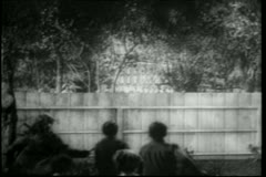 Rear view of children peering over wooden fence Stock Footage
