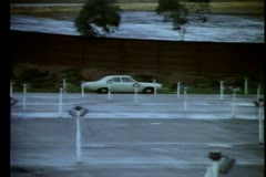 1970s car driving along empty drive-in Stock Footage
