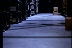 Low angle view of man chasing suspect in warehouse - stock footage
