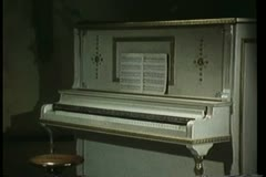 Wide shot of piano cover closing and sheet music falling Stock Footage