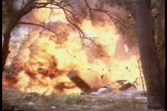 Wide shot of trailer blowing up in wooded area Stock Footage