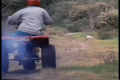 Stock Video Footage of Rear view of boy riding ATC on dirt road